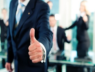 Business - team in an office; the senior executive has the thumb up; focus on thumb